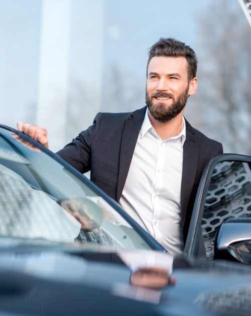 Portrait of a handsome businessman standing near the car outdoors near the modern building facade